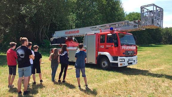 Menschen vor einem Feuerwehrfahrzeug mit Drehleiter.