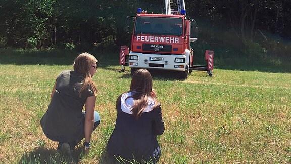 Feuerwehrdrehleiter im Einsatz am Baum. Zwei Menschen schauen zu.