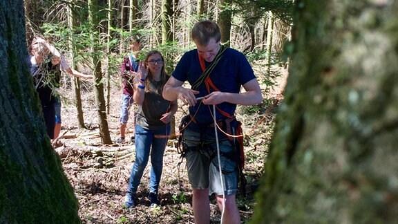 Ein Mann im Wald mit angelgtem Gurtzeug, beobachtet von drei Schülern