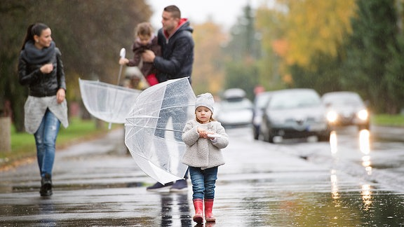 Eine Familie läuft im Regen auf einem Fußweg
