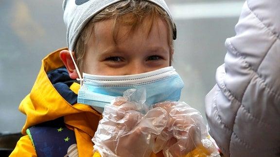 EIn Kind mit Schutzmaske und Handschuhen in der Moskauer Metro.