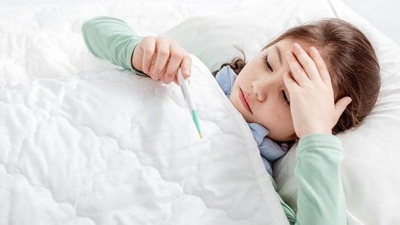 Krankes Kind mit Grippefieber, das im Bett liegt und ein Thermometer hält.