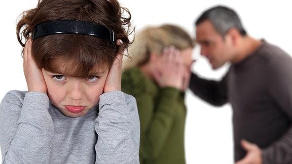 Ein Kind hält sich die Ohren zu, im Hintergrund streiten ein Mann und eine Frau