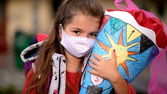 Ein Mädchen mit Schultüte und Corona-Maske