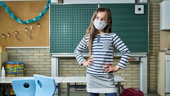 Junge Schülerin steht in Klassenzimmer, stützt Hände in Hüfte, trägt Maske und neigt Kopf leicht zur Seite, während sie in Kamera blickt