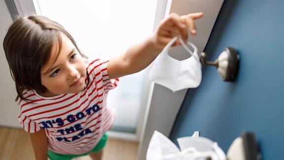 Bild von schräg oben: Kind greift nach FFP2-Maske an Haken