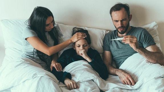 Mutter und Vater liegen mit Kind im Bett, Mutter hat besorgt Hand auf Stirn des Kindes, Kind hustet, Vater blickt besorgt auf Fieberthermometer