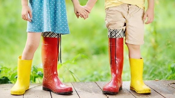Kinder mit roten und gelben Gummistiefel an den Füßen.