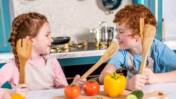 Zwei Kinder mit hölzernen Kochlöffeln in einer Küche