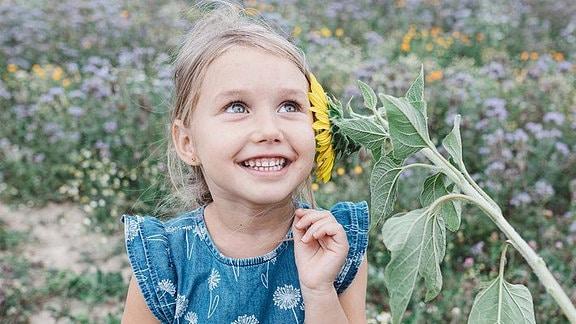 Einn Mädchen mit einer Sonnenblume am Ohr.