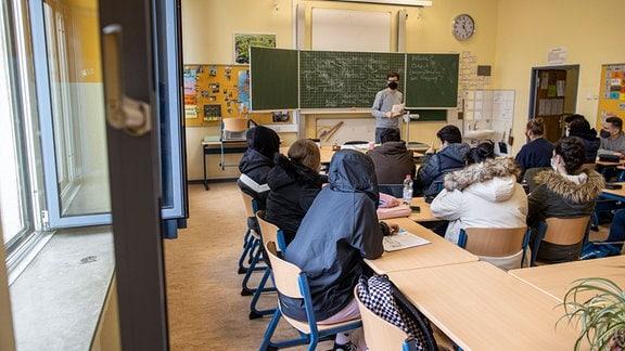Schulklasse im Unterricht bei geöffneten Fenstern.