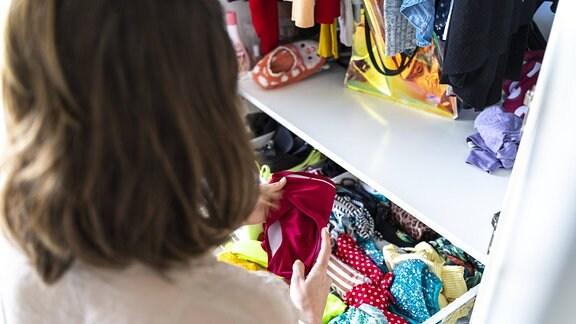 Eine Frau sortiert Wäsche in einemKleiderschrank.