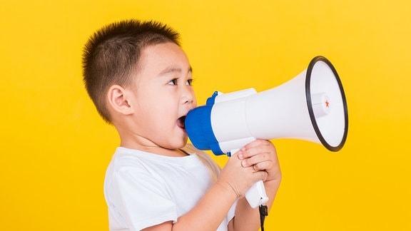 Ein kleiner Junge mit einem Megafon