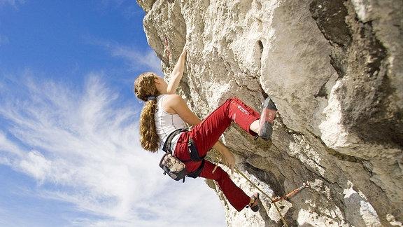 Eine Kletterin an einer Felswand.