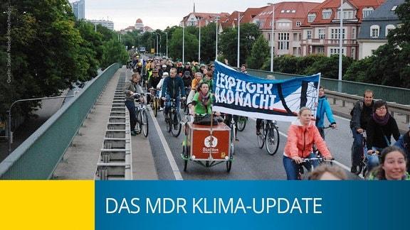 Eine Menschenmenge fährt mit Fahrrädern über eine Schnelltstraße in Leipzig.