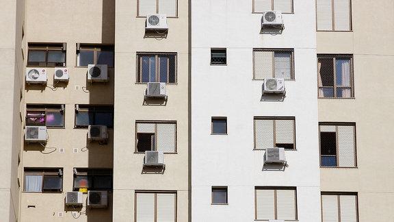 Ein Hochhaus mit vielen außen angebrachten Klimaanlagen.