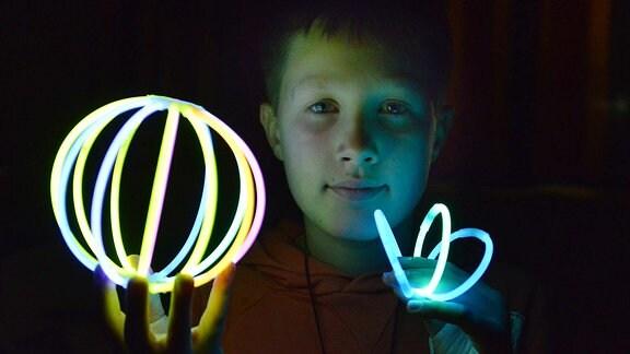 Kind spielt mit Knicklichtern.