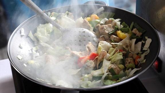 Gemüse und Fleisch wird in einem Wok zubereitet. Dampf steigt aus dem Wok.