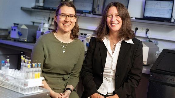 Zwei Frauen in einem Labor vor vielen Bildschirmen