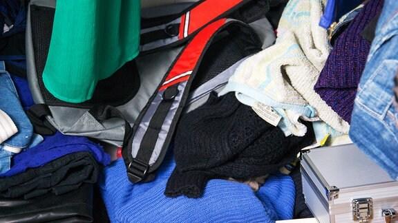 Kleidungsstücke, Taschen und Koffer liegen durcheinander auf dem Boden eines Kleiderschranks