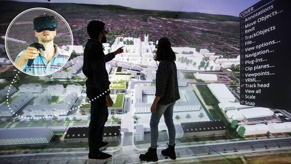 Zwei Menschen stehen vor der Projektion eines digitalen Raumes, an dessen Wänden eine Aufsicht auf ein Wohnviertel zu sehen ist. Auf einem kleinen runden Bild-im-Bild trägt ein Mann eine Virtual Reality-Brille.