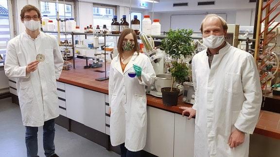 Dr. René Richarz mit einer Agarplatte mit dem Bakterium, Cornelia Hermes mit einem aus dem Bakterium gewonnenen Extrakt und Arbeitsgruppenleiter Dr. Max Crüsemann. Zwischen den Forschern steht eine Korallenbeere.