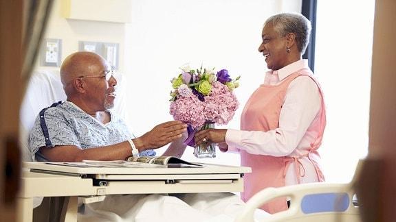 Eine Frau überreicht einem Mann im Krankenbett einen Blumenstrauß in einer Vase.