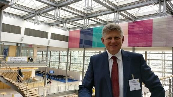Prof. Andreas Hochhaus vom Universitätsklinikum Jena steht in einer Messehalle.