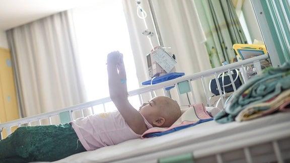 Krebskrankes Kind liegt in einem Krankenhausbett.