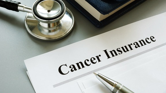 Auf einem Tisch liegt ein Stethoskop, ein Blatt mit der Überschrift 'Cancer Insurance' und ein Kugelschreiber.