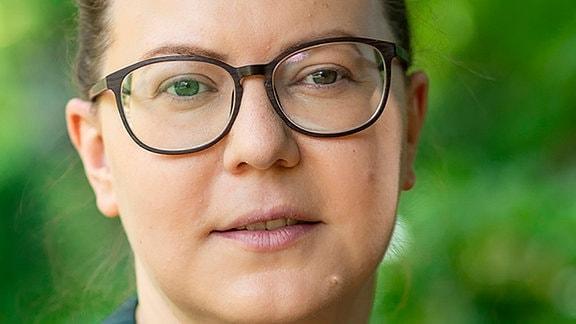 Porträtaufnahme einer weißen Frau mit zurückgebundenen Haaren, einer großen Brille und grüner Bluse