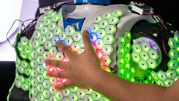 eine Hand greift auf den Brustkorb eines Roboters