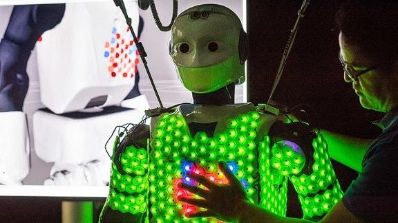 Ein Mann hält seine Hand auf den Brustkorb eines Roboters.