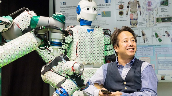 Ein Mann sitzt, hinter ihm steht ein Roboter.