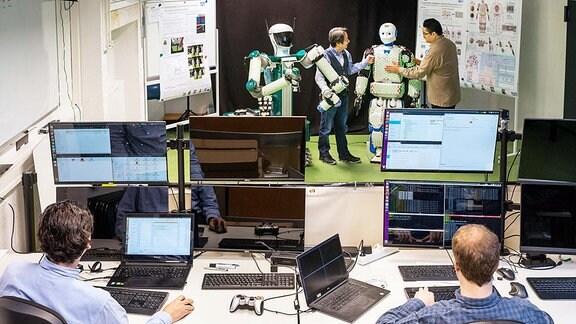 Ein Labor: im Vordergrund mehrere Menschen an Computern, im vorderen Bildbereich steht ein Roboter, und zwei Männer rechts und links neben ihm haben ihre Hände auf seinem Körper.