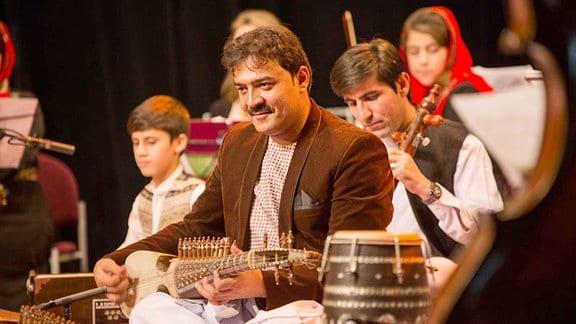 Mehrere Musiker, Erwachsene und Kinder, im Vordergrund sitzt ein Mann mit einer Laute.