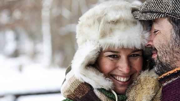 Eine Frau kuschelt sich an einen Mann; draußen im Winter, mit Winterkleidung