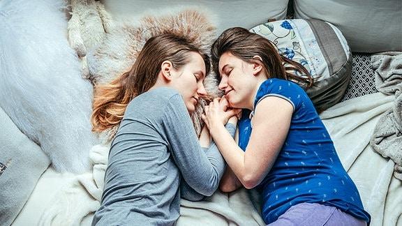 Zwei Frauen liegen aneinandergekuschelt nebeneinander.