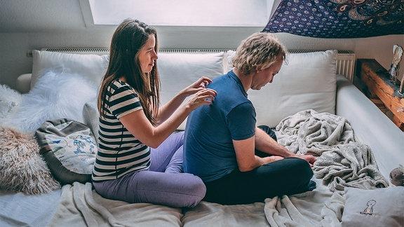 Ein Mann und eine Frau auf einem Bett