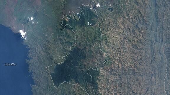 Die Satellitenaufnahmen von Landsat-5 (19. Juli 1986) und Landsat-7 (11. Dezember 2001) zeigen die Abholzung des Regenwaldes in Ruanda, Afrika.