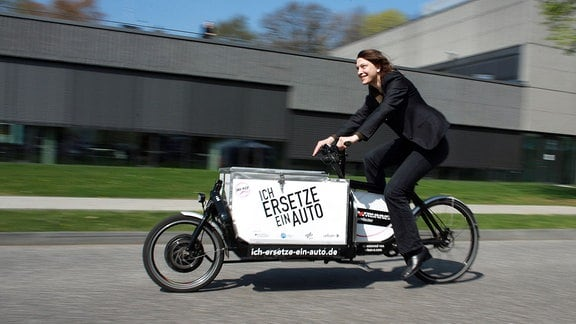 Eine Frau fährt auf einem Elektrolastenfahrrad bei einem Pressetermin im Deutschen Luft- und Raumfahrtzentrum (DLR) in Köln