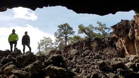 Zwei Forscher gucken in eine Höhle