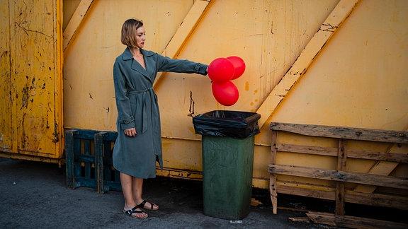 Junge Frau mt kinnlangen Haaren steht im Bademantel etwas teilnahmslos neben einer Mülltonne und ist dabei, mit ausgestrecktem Arm drei rote aufgeblasene Luftballons in eine Mülltonne zu werfen.