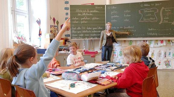 EIne Lehrerin steht an der Tafel vor vielen Schulindern in einem Klassenraum