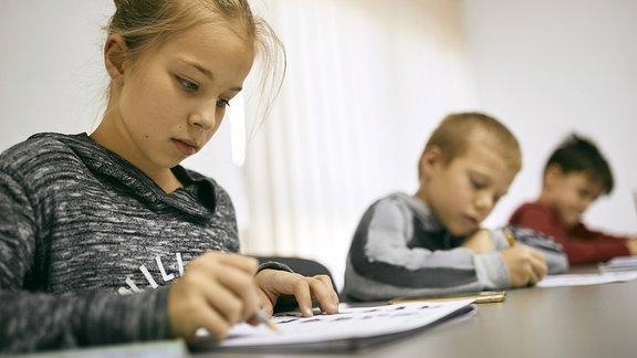Kinder lesen in Schulunterlagen.