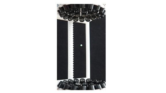 Schwebendes Kunststoffbällchen, gefangen in einem Feld von Ultraschallwellen, die von entgegengesetzten Transducern erzeugt werden.