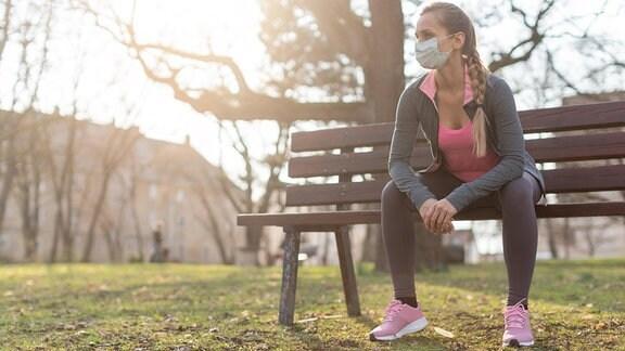 Frau in Sportkleidung mit Mund-Nasen-Bedeckung sitzt auf einer Bank im Park, kahle Bäume und leichtes Gegenlicht