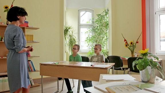 Zwei Jungen sitzen an einem Tisch und hören einer Frau zu.