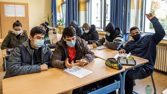 Schüler an der Globus Gesamtschule am Dellplatz sitzen in ihren dicken Winerjacken bei offenem Fenster in ihrem Klassenraum