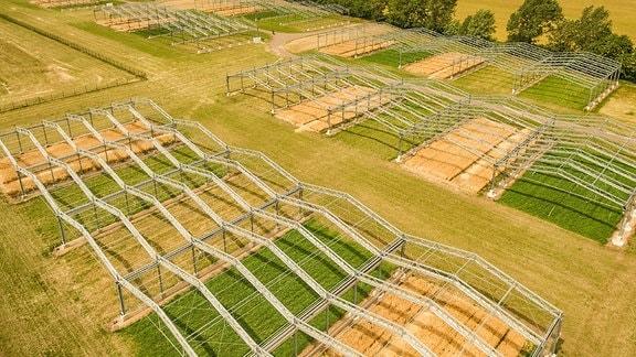 Luftbild von verschiedenen Feldern, die von Dachkonstruktionen umgeben sind: Global Change Experimantal Facility (GCEF) in Bad Lauchstädt, eine Experimentierfläche des Helmholtz-Zentrums für Umweltforschung (UFZ).